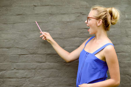 excited business woman: Copyspace picture of young excited beautiful lady in glasses pointing to the brickwall with pen. Concept of creativity