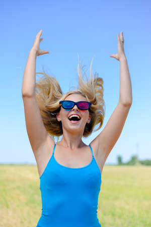 hands lifted up: Amazing picture of delighted happy young blond pretty lady in sunglasses with lifted arms over blue sky and yellow field on summer day outdoors background Stock Photo