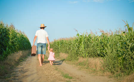 babygirl: Man and babygirl walking away on road between corn field over blue sky outdoors background. Backview of father carrying suitcase with daughter.