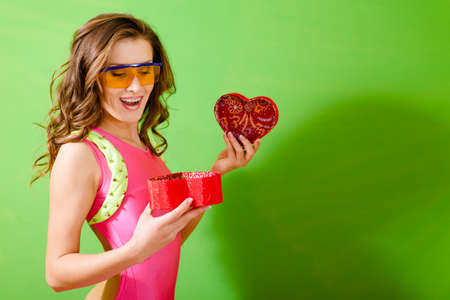 lycra: Woman wearing pink lycra jumpsuit and protect glasses with red giftbox. Half length of girl on bright green background.