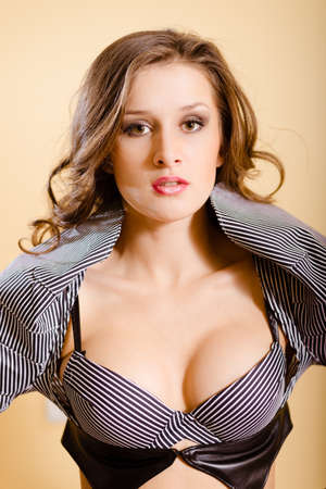 sexy boobs: Portrait of beautiful sexy girl with open mouth wearing striped bra . Young woman with curly hair on beige background.