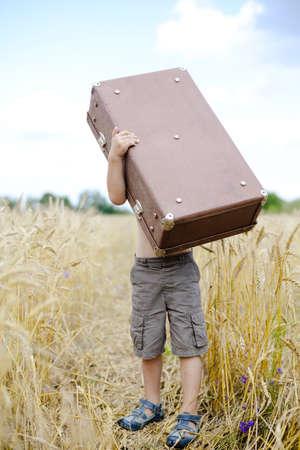 sandalia: Fotografía de un niño pequeño levantando gran maleta vieja en campo de trigo. Chico de cuerpo entero bajo valize marrón pesada sobre el fondo de cielo azul