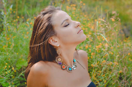 Portrait of young girl with fancy necklace and earrings. Pretty woman enjoying sunny day on blurred countryside meadow background. Stock Photo