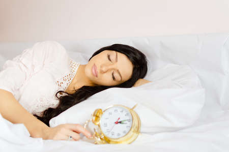 nightclothes: Picture of beautiful girl sleeping in white lace nightclothes. Young woman holding golden retro alarm clock on blurred indoor background.