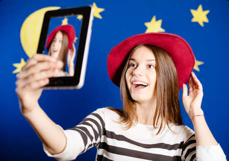 Picture of young woman trying on red hat and making selfie. Happy girl excited on stars and moon wallpaper background.