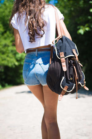 leather belt: Picture of young woman wearing jeans shorts walking away. Backview of girl with casual backpack on sunny countryside background.