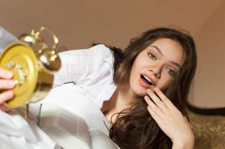oversleep: Picture of pretty girl lying with open book holding alarm clock. Young woman surprised and looking oversleep on blurred indoor background.