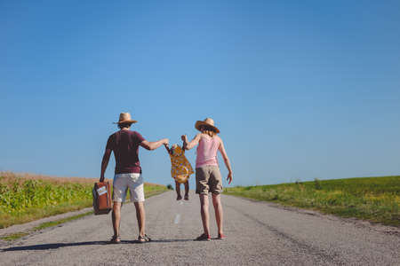 highway 3: Picture of man and woman swinging little baby girl on road. Backview of happy family with retro suitcase waiting on highway on blue sky outdoor background.