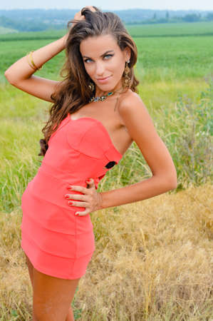 Picture of pretty girl wearing coral mini dress and fancy necklace. Sexy lady with tangled hair smiling on summer countryside outdoor background.