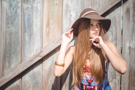 animal woman: Picture of young beautiful lady in brown hat and tiger print top. Pretty girl standing on old wooden fence countryside background.