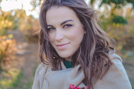 joyfull: Portrait of charming woman in cozy coat gently smiling. Closeup of happy girl with tangled hair on blurred autumn outdoor background. Stock Photo