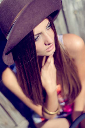 light hair: Portrait of young lady in pale purple hat looking at distance. Pretty woman in colorful top sitting on summer blurred outdoor background.