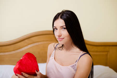 camisole: Picture of charming girl in silk camisole holding red heart shaped gift box. Young woman with long hair looking at camera on bedroom indoor background.