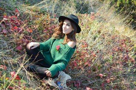 joyfull: Picture of young girl in black hat and sweater sitting on dried grass with read leaves. Pretty woman smiling on sunny autumn outdoor background.