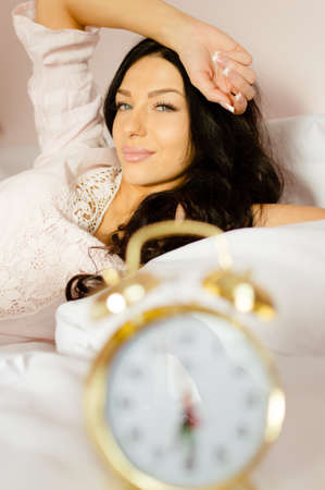 nightclothes: Portrait of charming girl with long tangled hair awaking in lace nightclothes. Young woman smiling gently with retro alarm clock as blurred foreground. Stock Photo
