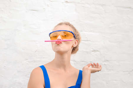 clowning: Portrait of funny girl balancing with pencil on lips. Young woman wearing big protecting glasses on white wall outdoor background. Stock Photo