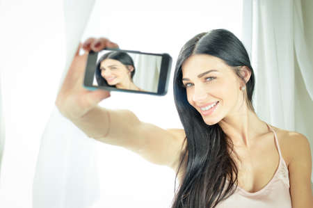 camisole: Portrait of beautiful exciting young woman in silk camisole making selfie beside morning window. Charming girl happy smiling on white blurred indoor background. Stock Photo