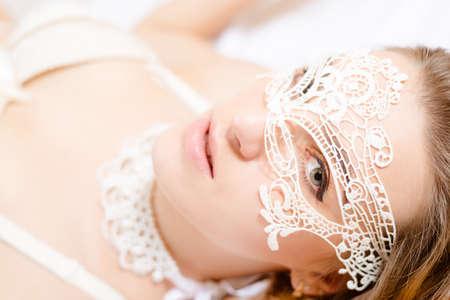 豪華なスタイルの素敵な美しい女の子のポートレート、クローズ アップ。光の背景に白のビスチェ着用レースのマスクのセクシーな女性。