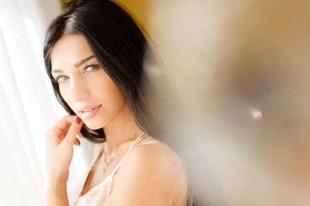 femme se deshabille: Close up portrait de la belle jeune femme de d�tente � la fen�tre et heureux regardant la cam�ra