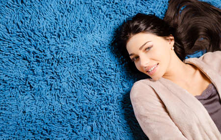 carpet and flooring: Portrait of happy beautiful young lady in beige robe looking at camera laying on blue fluffy carpet. Closeup of charming brunette with long hair on blue soft background.