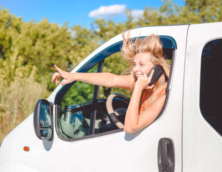 handsfree phone: Portrait of blond girl in white car speaking by phone and looking from car window. Young woman excited and smiling while talking with someone and pointing up on summer countryside background.