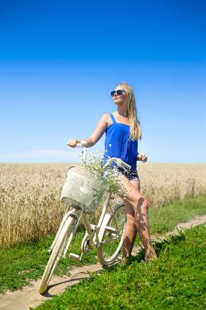 mujer sexy: Imagen de chica sexy rubia en bicicleta blanca con cesta de flores. La chica joven en gafas de sol relajado en fondo soleado campo de verano.