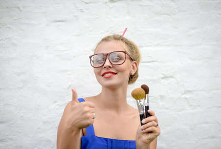 one people: Portrait of blond girl in hipster glasses thumbing. Young woman holding makeup brushes and happy smiling on white wall background.