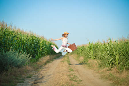 exciting: Picture of amazing girl wearing straw hat jumping with suitcase on road in corn field. Side view of happy exciting young lady in white costume on sunny blue sky background. Stock Photo