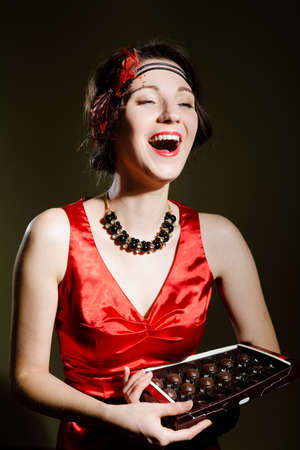 background box: Portrait of elegant beautiful girl in vintage dress laughing and holding box of chocolate sweets. Pretty woman in art deco styled red gown on dark blurred background.