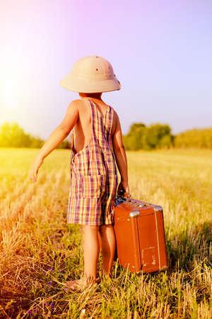 médula: Vista posterior de la imagen del niño pequeño que llevaba sombrero de explorador y el mameluco de la tela escocesa estuche valize marrón grande en el campo. Niño en el sombrero del safari que mira hacia atrás en el cielo azul al aire libre fondo