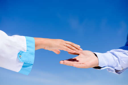 Closeup picture on handshake between a man and a doctor over blue sky on sunny day outdoors background