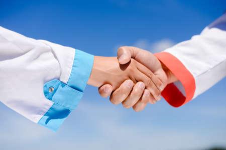 Handshake between doctors over blue sky sunny outdoors background, closeup picture Stock Photo