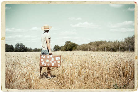 framed picture: Picture of man in straw hat with old suitcase standing on wheat field. Framed image in vintage paper photo style.