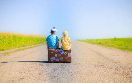 Back view picture of children sitting on the suitcase over countryside rural road on sunny blue sky outdoors background