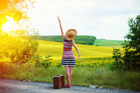 Picture of young woman in straw hat with retro suitcase beside beautiful summer meadow. Backview of girl standing on sun flare country roadside background. 版權商用圖片 - 45881837