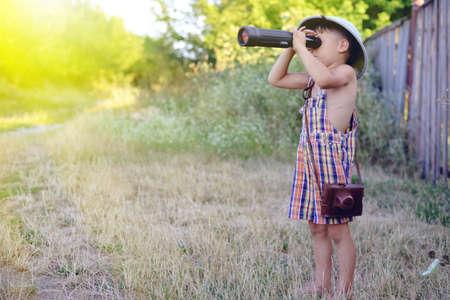 médula: Fotografía de un niño que lleva el mameluco de la tela escocesa que mira en catalejo cerca de cerca de madera vieja. Pequeño explorador con camerabag en el fondo campo soleado. Foto de archivo