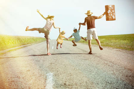 Picture of happy amazing family holding each other hands in summer. Backview of exciting parents and two kids jumping with suitcase on sunny countryside background.