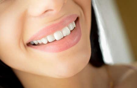 美しい笑顔の写真。白い歯と屋内背景をぼかした写真に自然な唇のクローズ アップ。 写真素材