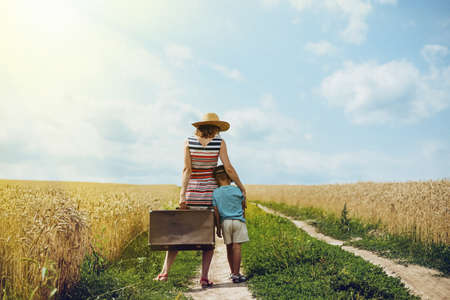 together standing: Picture of woman and little boy standing in middle of country road. Mother and son travelling together with old suitcase on summer sky outdoor background.