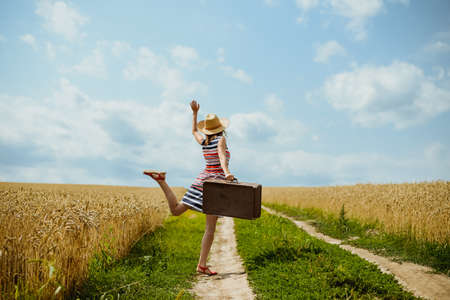 Picture of woman wearing striped dress dancing on country road. Backview of young girl holding retro suitcase on the blue sky sunny outdoors background.