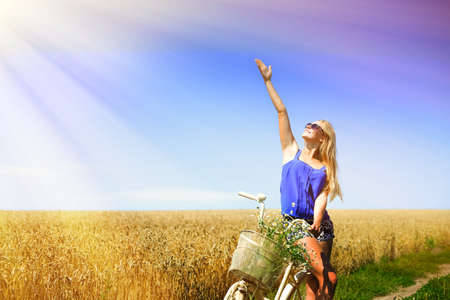 woman hands up: Picture of sexy girl excited on white bike with flower basket in wheat field. Young woman pointing on sunlight and standing on  flare countryside background.