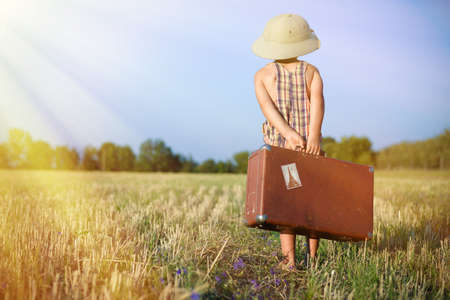 Picture of little boy wearing pith helmet carrying old suitcase in countryside. Backview of kid in plaid romper walking away on sunny flare background.