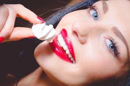 白いマシュマロを保持している美しい若い女性の肖像画。赤い唇と幸せ笑顔暗い背景の青い目を持つ少女。