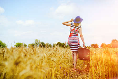 Picture of young woman in blue hat with suitcase walking away through golden wheat field. Backview of girl in striped dress in direct sunlight on summer countryside background.