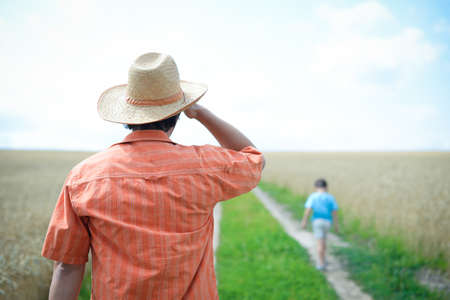 next horizon: Man wearing straw hat looking after little boy walking away. Kid walking by countryside road near field over blue sky sunny outdoors background