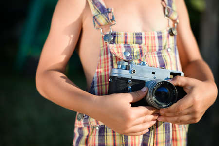 romper: Closeup picture of vintage camera which is holding by child hands. Boy wearing plaid romper in summer countryside.
