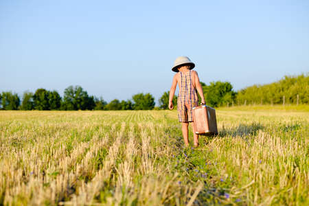 pith: Picture of little boy wearing plaid romper and pith helmet carrying big suitcase in grass field over blue sky sunny outdoors background. Kid in safari helmet walking away.