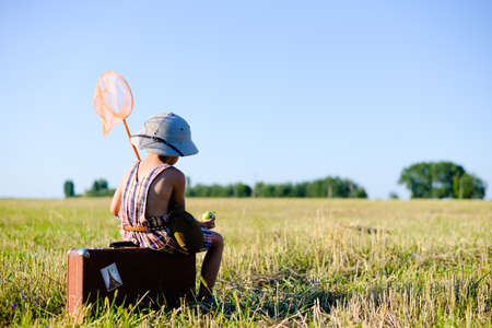 butterfly net: Picture of sweet small boy sitting on old brown suitcase eating green apple. Kid has ring net and flask over blue sky sunny outdoors background