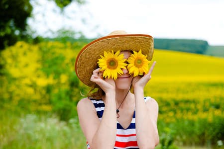 two and a half: Young pretty lady wearing straw hat with two sunflowers instead glasses. Half length of smiling girl on countryside background.