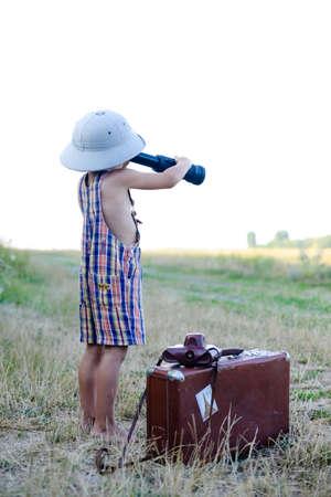 m�dula: Mameluco del ni�o que llevaba a cuadros y sombrero de explorador que mira en catalejo cerca de la maleta grande. Backview del peque�o explorador con valize en el fondo del campo de hierba.